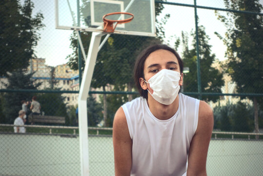 Teenager wearing a protective mask resting in front of basketball hoop