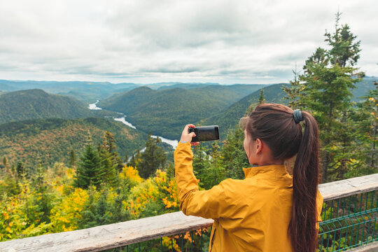 Tourist taking phone photo of autumn landscape view from Canada travel destination. Woman hiking in outdoors nature forest.