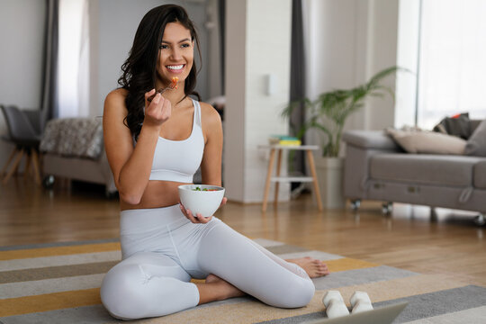 Fit woman eating healthy salad after working out at home