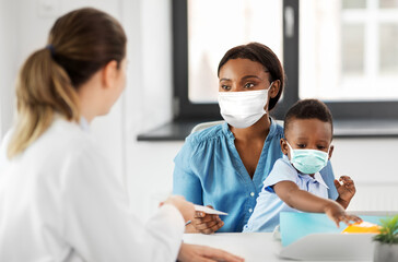 medicine, healthcare and pediatry concept - caucasian doctor giving prescription to african...