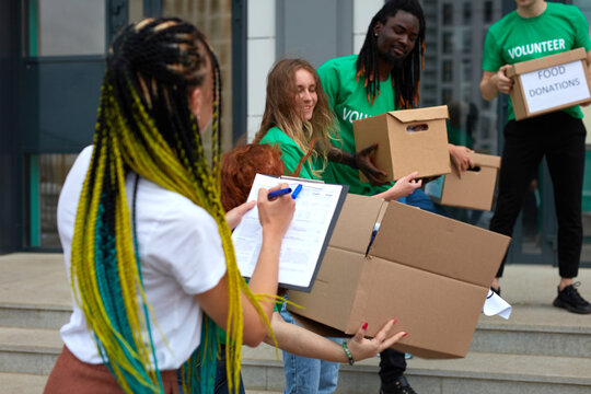 active young people enjoys volunteering at food and clothes bank, voluntary company. diverse people working in voluntary company with friends putting food for donation into boxes