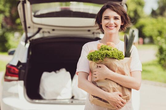 Portrait of positive brown hair girl enjoy ride drive car supermarket buy eco ecological food for vegetarian dinner hold paper bag in town center outside