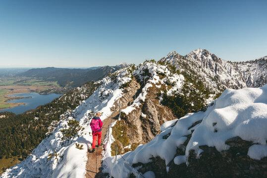 Wanderin im Neuschnee auf dem Gratweg zwischen Heimgarten und Herzogstand mit Blick auf den Kochelsee und Herzogstand-Gipfel