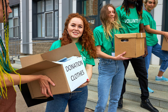 friendly interracial charity group engaged in voluntary, they stand outdoors on stairs transfering boxes with food and clothes, donation concept