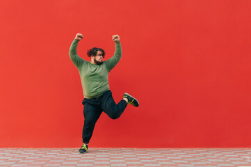 Portrait of funny fat dancer in casual clothes dancing on red wall background and looking aside at...