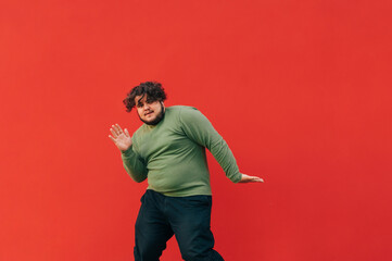 Charismatic young man with curly hair and overweight dancing hip hop on the street on a red background. The fat man shows a dance performance, isolated.