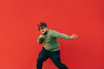 Expressive overweight young man in stylish casual clothes dancing hip hop on red wall background. The fat man shows a dance performance.