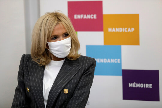 French President Emmanuel Macron's wife Brigitte Macron listens to volunteers of the association OSE, which takes care of sick and disabled children in Paris