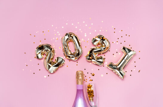 2021 golden foil balloons numbers, champagne, stars confetti, ribbons  and bokeh. Top horizontal view copy space new year and holiday concept.