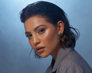 Obraz Closeup fashion face studio portrait. Tanned caucasian brunette woman. Fashionable stylish female model with makeup and wet hair against smoke at background - fototapety do salonu