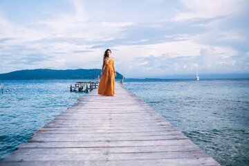 Full length portrait of beautiful Caucasian tourist walking at wooden pier during solo journey for exploring Dominican Republic, young woman recreating on Costa Rica during summer resort vacations Wall mural