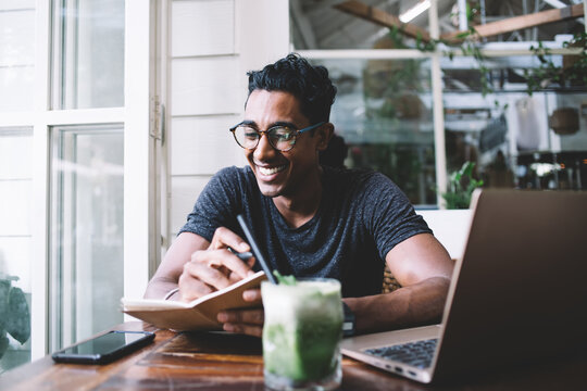 Positive ethnic writer writing in journal while sitting at table with gadgets and refreshing drink