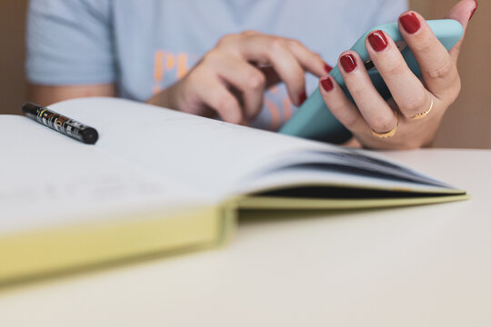 Woman with red nails typing on her phone and typing on her notebook