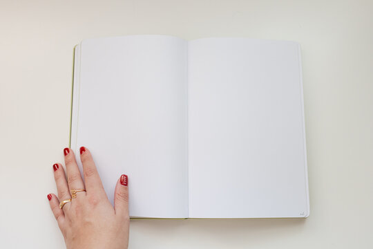 White notebook with copy space. Woman hand with red nails polish and gold rings