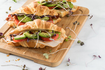 Three freshly made croissant sandwiches on a wooden board ready for eating.