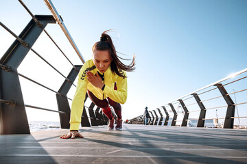 Photo sur Plexiglas Dinosaurs outdoor workout concept. young woman in tracksuit performs sports workout on the pier