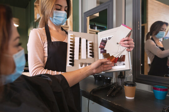 Female hairdresser wearing face mask showing hair color sample chart to female customer