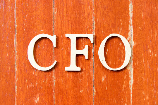 Alphabet letter in word CFO (Abbreviation of Chief Financial Officer) on old red color wood plate background
