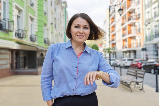 Portrait of middle aged confident business woman in city