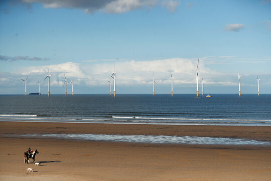 Wind turbines are seen in the background as people stroll along Redcar Beach in Redcar
