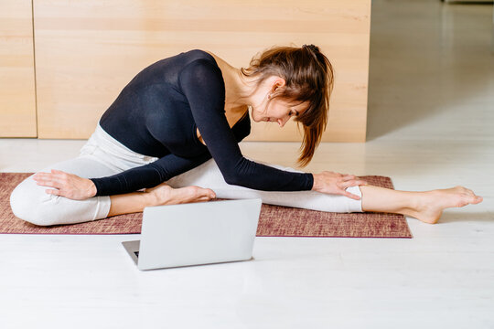 Fitness virtual online exercise. Woman Stretching from internet at home. A sporty girl in sportswear working out. Workout training in living room. Young woman laptop and foam roller a side