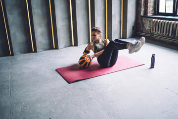 Concentrated woman doing sit ups with ball