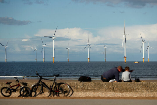 Wind turbines are seen in the background as people sit at Redcar Beach in Redcar