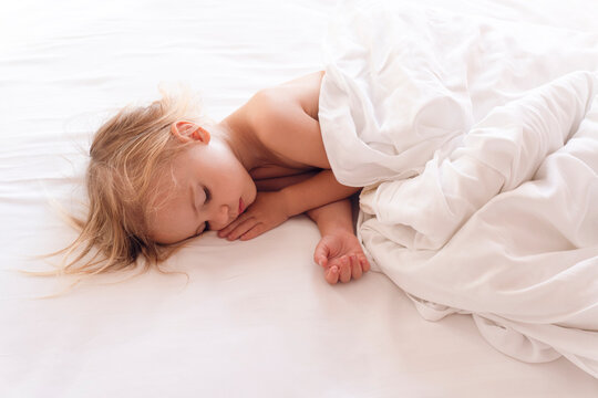 View at the little lovely sleeping caucasian baby and white sheets, childhood concept, copy space.