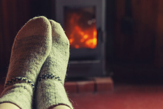Feet legs in winter clothes wool socks at fireplace background. Woman sitting at home on winter or autumn evening relaxing and warming up. Winter and cold weather concept. Hygge Christmas eve.