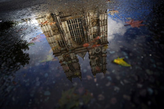 Westminster Abbey is reflected into a puddle in London