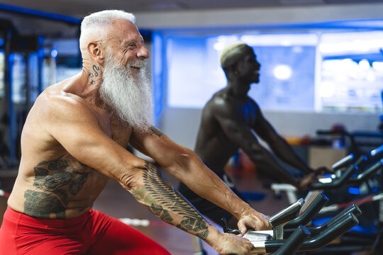 Senior and young men doing bike exercises in gym - People with different age and race training on cycling machine in health wellness center - Sport activity and fitness lifestyle concept