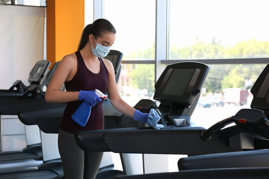 Woman cleaning treadmill with disinfectant spray and cloth in gym