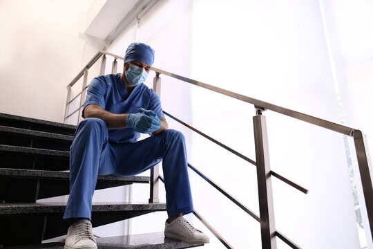 Exhausted doctor sitting on stairs indoors. Stress of health care workers during COVID-19 pandemic