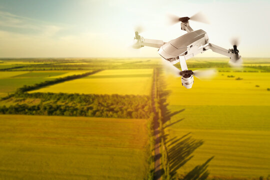 Modern drone flying over fields on sunny day. Aerial survey