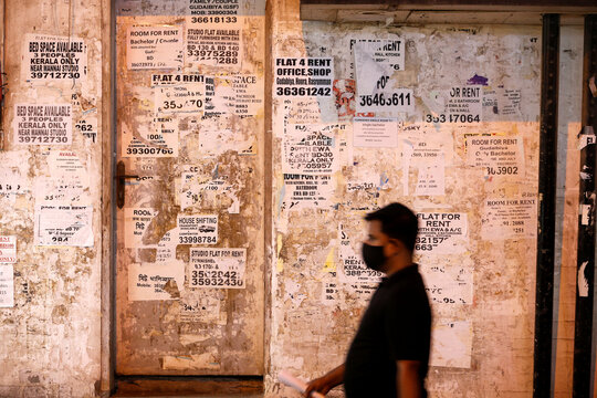 A man wearing a face mask passes in front of a wall with property rental adverts displayed in bulk, following the outbreak of the coronavirus disease (COVID-19), in Manama
