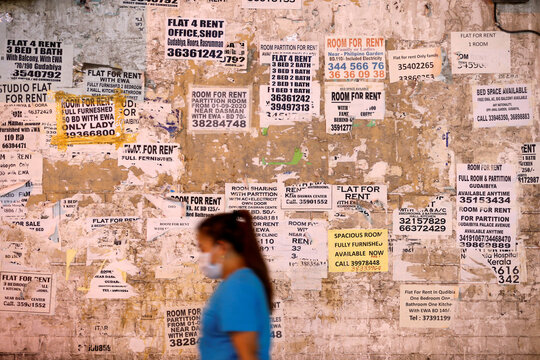 A woman wearing a face mask passes in front of a wall with property rental adverts displayed in bulk, following the outbreak of the coronavirus disease (COVID-19), in Manama