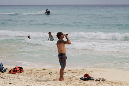 A tourist drinks a beer at a beach as the Hurricane Delta approaches, in Cancun