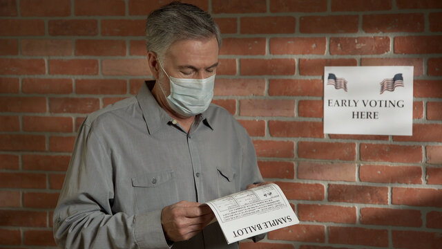 man with a mask during covid-19 looking at a sample voting ballot