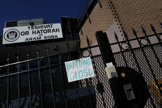 A sign is seen at a locked gate to the closed Yeshivat Or Hatorah school amid the coronavirus disease (COVID-19) outbreak in the Sheepshead Bay section of the Brooklyn borough of New York