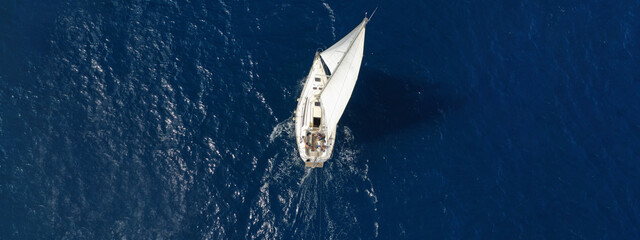 Aerial drone ultra wide photo of sail boat cruising deep blue Ionian sea