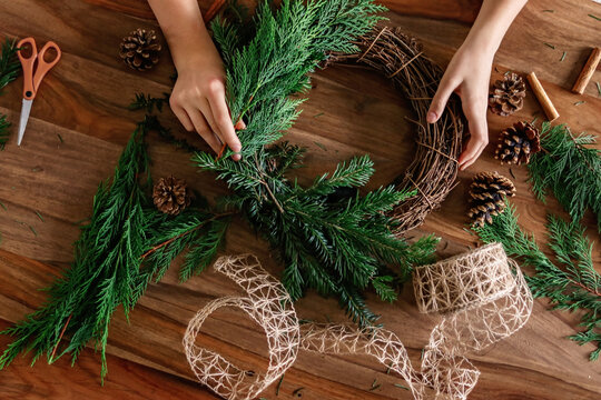 Overhead shot of hands making handmade Christmas wreath with twigs, pine cones, cinnamon sticks, yew and thuja branches and natural string. DIY home decor.