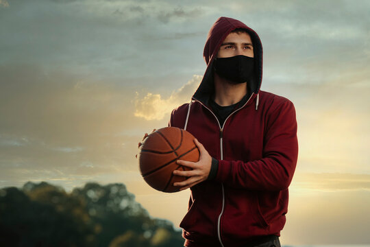 A young man with a face mask holding a basketball.