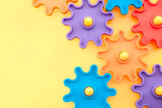 Teamwork and solidarity concept with photograph of connected colorful plastic toy gears with each gear a different color isolated on yellow background with copy space