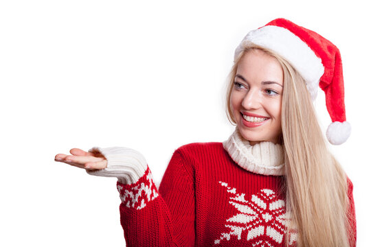 cute blond woman with santa hat and knitted sweater presents a fictive virtual product or advertising message by holding out her hand. free copy space on the left for your commercial creativity.