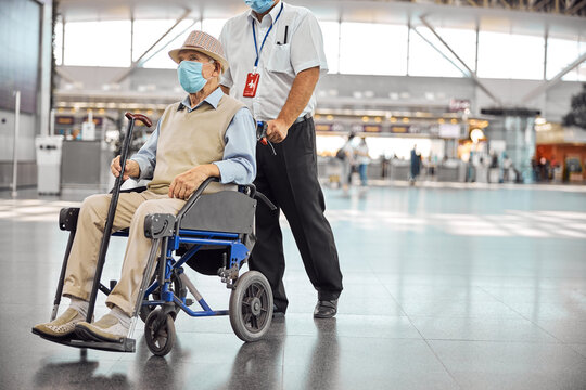 Airport worker rolling a wheelchair with a senior man