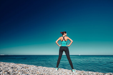 Female having workout on coastline. Fresh air and blue cloudless sky. Active lifestyle and fitness...