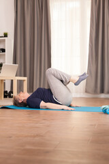 Elderly age woman doing abs physical training in living room on the yoga mat. Old person pensioner...