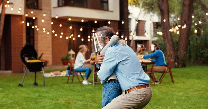 Caucasian happy grandfather and small cute granddaughter in medical face shields hugging in yard. Family at table with barbeque dinner on background. Senior grandpa embracing little girl in masks.