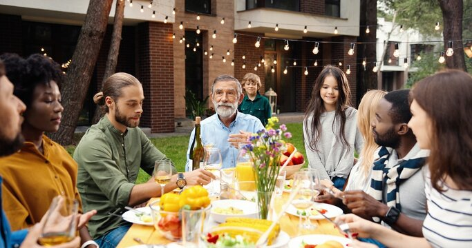 Multi ethnic family sitting at table with meal outdoor at picnic and senior man saying toast. Mixed-races happy young and old people having dinner and toasting at party barbrque Celebration on weekend