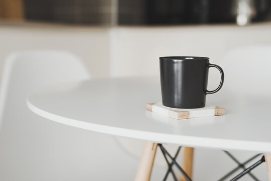 Empty black coffee mug stand on a marble coaster at the kitchen table
